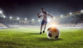 Soccer player at stadium. Mixed media. Sport arena and soccer player with ball. Mixed media royalty free stock photo
