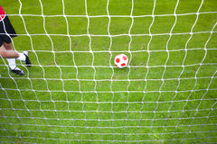 Soccer player standing near ball and goal net Royalty Free Stock Photography