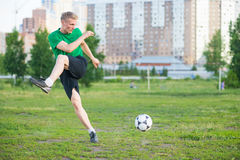 Soccer player strongly hits the ball. Stock Photos
