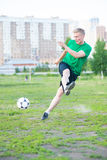 Soccer player strongly hits the ball Stock Images