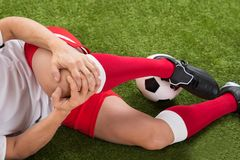 Soccer player suffering from knee injury. Close-up Of Male Soccer Player Suffering From Knee Injury On Field Royalty Free Stock Images