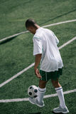 Soccer player training with ball on soccer pitch Royalty Free Stock Images