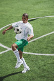 Soccer player training with ball on soccer pitch Stock Photo