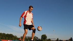 Soccer player is training and bouncing a soccer ball by his foot. Man kicks the ball by his feet during the session, shooting point from the bottom, white and stock footage
