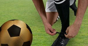 Soccer player tying his shoes with golden ball. Digital composite of soccer player tying his shoes with golden ball Royalty Free Stock Photography