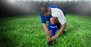 Soccer player tying shoelace on field. Digital composite of Soccer player tying shoelace on field Stock Photos
