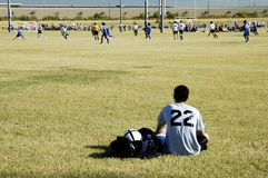 Soccer player watching the action. A soccer player relaxes while watching a game in process Royalty Free Stock Image