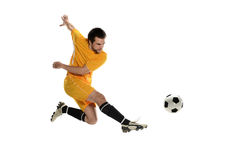 Soccer player. Wearing a yellow uniform kicking the ball on a white background Stock Photo