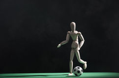 Soccer player. A wooden mannequin playing soccer on a green surface. The background is black Royalty Free Stock Photos