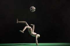 Soccer player. A wooden mannequin playing soccer on a green surface. The background is black Royalty Free Stock Image