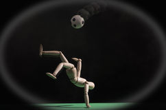 Soccer player. A wooden mannequin playing soccer on a green surface. The background is black Royalty Free Stock Images