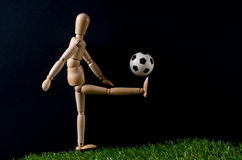 Soccer player. A wooden mannequin playing soccer on a green surface. The background is black Stock Image
