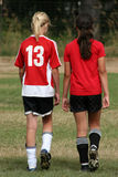 Soccer players. Two girls walking away next to each other in soccer uniforms Royalty Free Stock Photos