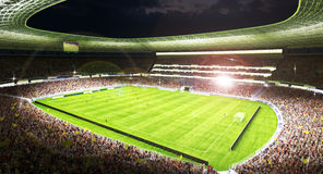 Soccer players in action at a grand soccer arena at night Royalty Free Stock Image
