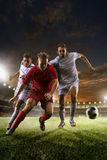 Soccer players in action on sunset stadium background Royalty Free Stock Image