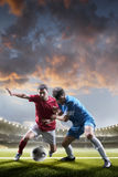 Soccer players in action on sunset stadium background stock photo