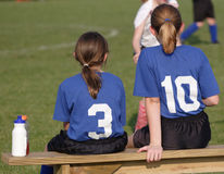 Soccer Players on Bench. Girl soccer players on sidelines bench during game with pony tails Stock Photography
