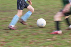 Soccer players blur. Motion blurred picture of two soccer players - focus on the ball Stock Images