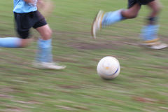 Soccer players blur. Motion blurred picture of two soccer players - focus on the ball Stock Image