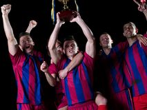 Soccer players celebrating victory. Soccer players team group celebrating the victory and become champion of game while holding win coup Stock Images
