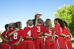 Soccer Players With Coach. Rear view of multiethnic football players standing in front of coach Royalty Free Stock Image