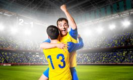 Soccer players. Soccer or football players are celebrating goal on stadium Stock Photos