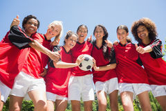Soccer players gesturing thumbs up. Portrait of successful female soccer players gesturing thumbs up against clear blue sky Stock Photos