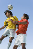 Soccer Players Heading Ball Against Blue Sky Royalty Free Stock Photo