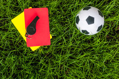 Soccer players outfit on green field or lawn of stadium with referee red yellow card and football ball Stock Photography