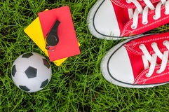 Soccer players outfit on green field or lawn of stadium with referee red yellow card and football ball Royalty Free Stock Photo