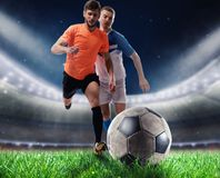 Soccer players play with soccerbal at the stadium Royalty Free Stock Image