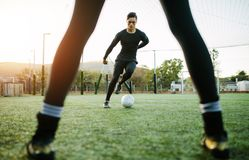 Soccer players during practice. On football ground. Young footballer playing on the grass field Stock Photography