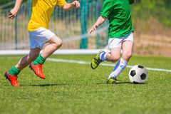 Soccer players running with ball. Football soccer match for kids Stock Photos