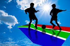 Soccer players in silhouette. Two young soccer or football players and a ball in silhouette on a colored panel for the flag of South Africa Stock Photo