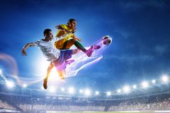 Soccer players on stadium in action. Mixed media stock photography