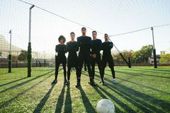 Soccer players standing together on pitch. Full length of five a side football team on field during training. Soccer players standing together on football pitch Stock Images