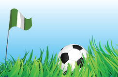 Soccer playground, nigeria. An illustrations of soccer ball, with a nigeria flag waving at the background Royalty Free Stock Image