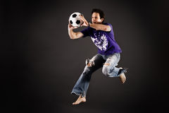 Soccer playing catching a ball. In the studio Royalty Free Stock Photography