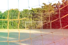 Soccer posts in park, field is partially covered in the shadow. Trees in the background are in the sun. Rio de Janeiro, Brazil. Co. Soccer posts in park, field Royalty Free Stock Photo