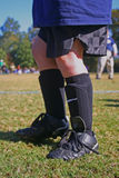 Before soccer practice. Young boy's legs with soccer cleats and shinguards Stock Photography