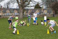Soccer Practice. Adults on grassed area with school children supervising a football training session, Everyone can be seen running around cones. School building Stock Photos