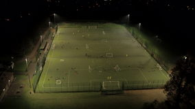 Soccer Practice on a Floodlit Astroturf Pitch. Aerial Clip of children and adults playing football on a floodlit astroturf pitch at night. The teams are playing stock video