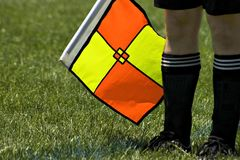 Soccer referee with flag. Soccer referee with a yellow and orange flag Stock Photo