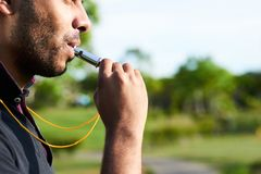 Soccer Referee Focused on Work. Close-up shot of bearded soccer referee blowing whistle after noticed infringement of game rules, blurred background Stock Photos