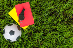 Soccer referee outfit a yellow and red card with ball on lawn of stadium. Football background Royalty Free Stock Image
