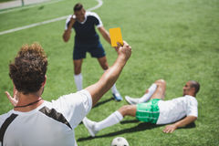 Soccer referee showing yellow card to players during game. Back view of soccer referee showing yellow card to players during game Royalty Free Stock Photos