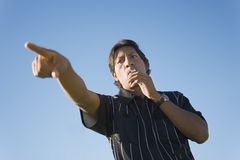 Soccer Referee Whistling. Low angle view of soccer referee whistling to start the match Royalty Free Stock Images