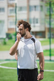 Soccer referee whistling in whistle on soccer pitch during game Royalty Free Stock Image