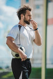 Soccer referee whistling in whistle on soccer pitch during game. Side view of soccer referee whistling in whistle on soccer pitch during game Royalty Free Stock Photos