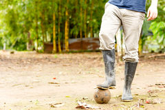 Soccer In Rubber Boots. Soccer Theme With Rubber Boots And Aged Ball In Ecuadorian Jungle Royalty Free Stock Photos